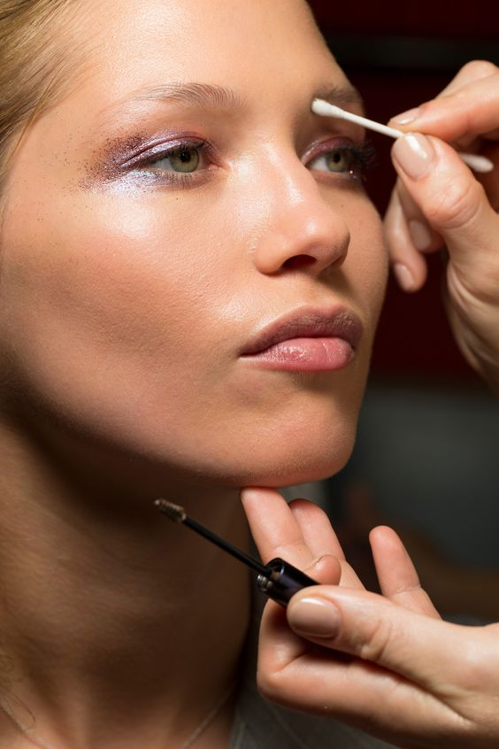 10 tools all beauty editors use religiously and you should too. Here, a model backstage has a cotton bud applied to her eyebrow during make-up application before a runway show.