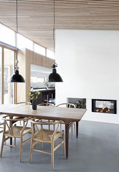 Scandinavian dining space with dining table and Y Chairs by Hans J. Wegner. The industrial pendants are a cool contrast to the nordic interior.