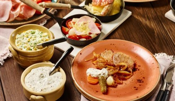 """Saftiges Schweinefilet, deftiger Frühstücksspeck, etwas Sauerkraut, knackige Kirschtomaten, Mixed Pickles und Würstchen benötigt man für das Raclette """"rustikal"""". Dazu noch ein würziger Meerrettich-Dip und einen scharfe Chiligurken-Remoulade und es kann losgehen!"""