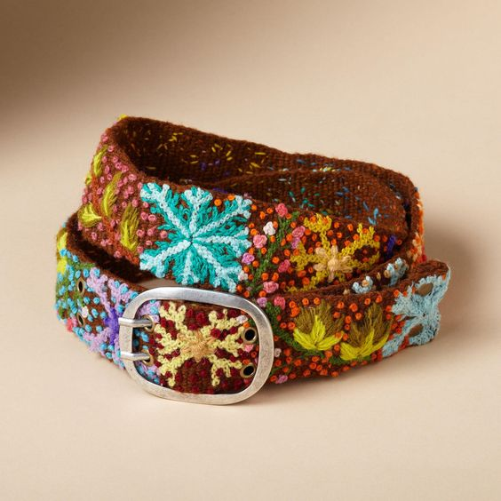 """NOMAD DELIGHT BELT--Embroidered by artisans in Peru with snowflakes and festive flora, our sturdy wool belts brighten any winter wardrobe. Each handmade belt varies slightly. Imported. Sizes S (23"""" to 31""""), M (28"""" to 37""""), L (34"""" to 43""""). 2""""W."""