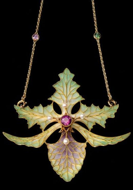 An Art Nouveau gold, plique-à-jour enamel, pearl and ruby pendant, by Georges Fouquet, circa 1898. The pendant designed as an orchid decorated with plique-à-jour enamel, centring a round faceted ruby, surrounded by four small pearls set to the anthers, mounted in yellow gold, suspended from a gold chain set with gems. Collection of Mikimoto Pearl Museum. #Fouquet #ArtNouveau #pendant: