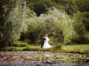 Couple kissing surrounded by lush beautiful water gardens