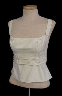 Rare soft wrap corset, c.1810-1820. Made from ivory cotton and completely hand stitched, the corset has gathered bust inserts and triangular side-hip inserts as the only shaping. It is laced only at the upper back opening. Waistline ties wrap around and pin in front. The corset was likely meant more for modesty under a sheer dress than for significant support. The soft, wrap-style is rarely found.