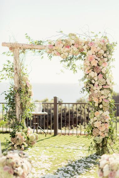 An asymmetrical design took this chuppah a more organic route. Love the overgrown feel and the exposed wood! | Design by Hidden Garden Flowers, Photo by Figlewicz Photography