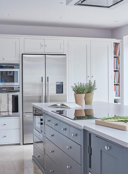 a ceiling mount vent hood stands over a blue kitchen