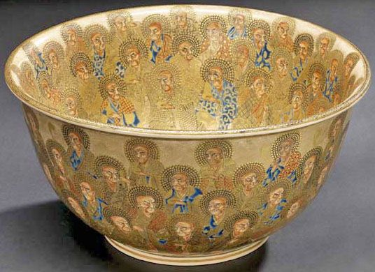 """A Japanese Satsuma porcelain punch bowl, decorated in traditional enamels and gildingon the interior and exterior with continuoius scenes of robed """"saints"""" against an oatmeal-colored ground, Japan, circa 1868-1911"""