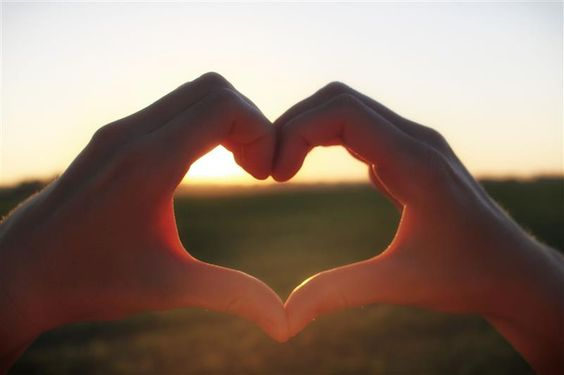 Woman shows heart from hands at sunset