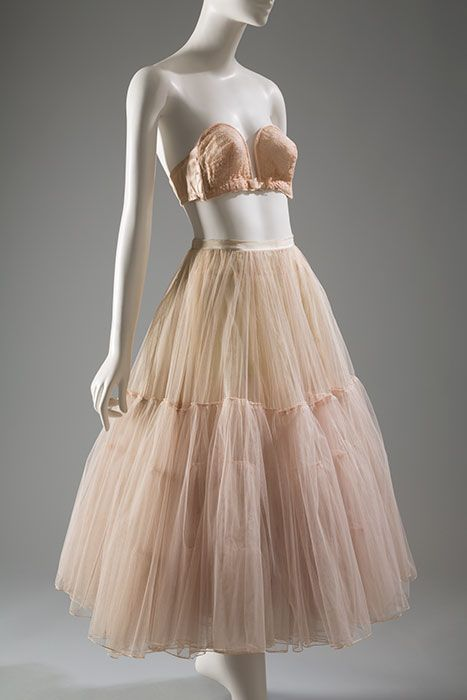 """Christian Dior's 1947 """"New Look"""" collection heralded a return to the hourglass silhouette. The bust became a focal point, and its shape was defined by a variety of highly structured bras and corselets. Petticoats were often worn to maintain skirt fullness. This petticoat by Dior was made especially for one of his couture gowns."""