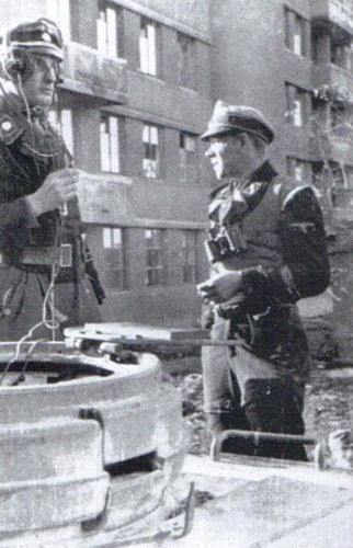 "Kharkov 1943, Kampfgruppe ""Kuntsmann"". 7.Kp./SS-Pa.Regt.3 is part of it. Its chief SS-Oberturmführer Behr, is on the left with the headphones. One of his section chiefs share a brief respite with him"