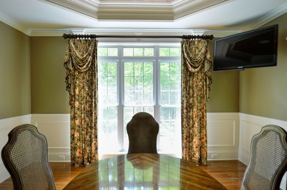 http://curtaincallct.com/ Custom made stationary drapery panels with swags and black and brown tassel trim in a dining room