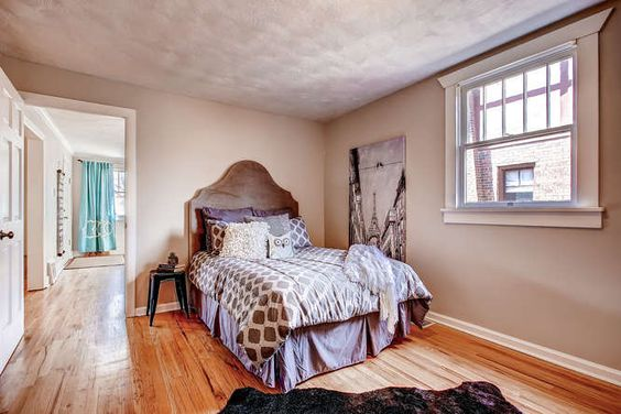 shades of brown and gray in the bedroom totally work with graphic art and hardwood floors.