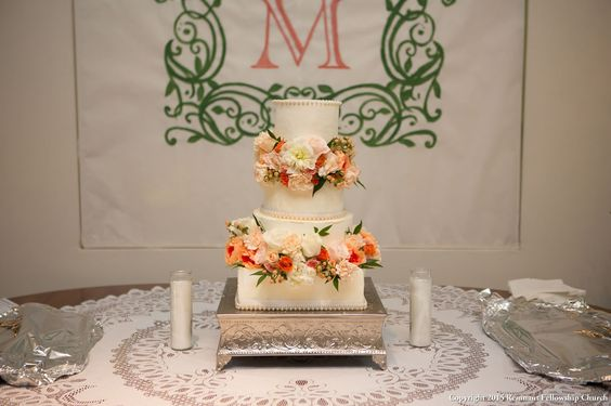 Summer wedding cake tiered white wedding cake with coral and peach flower accents