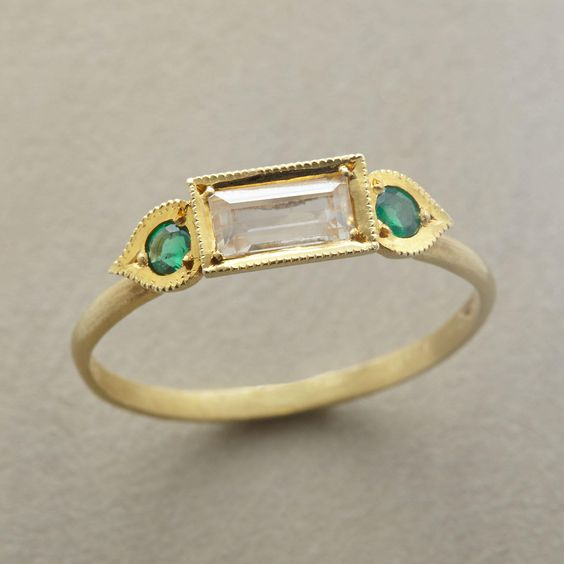 UMA RING--A white sapphire and emerald ring, in which Ila and Vikas chose rich green emeralds to accentuate the absence of color in a singular white sapphire baguette. Handcrafted in USA of matte 14kt gold. Whole sizes 5 to 8.