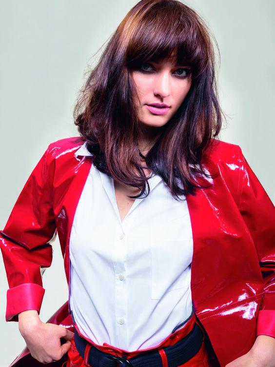 chica con blazer de charol rojo y camisa blanca con pelo moreno largo con flequillo