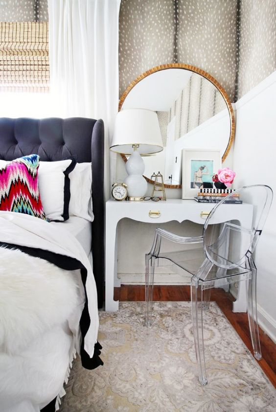 Chic bedroom featuring a chic side table/ vanity with a lucite chair and gilded mirror: