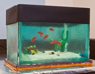 Aquarium cake! How in the world? Sheets of melted candy I bet for the glass and the fish hanging from the top. Oh how fun is that?: