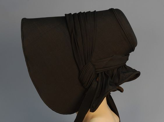 Black bonnet with pleated self trim, wide bavolet, and satin ties, c. 1840s.