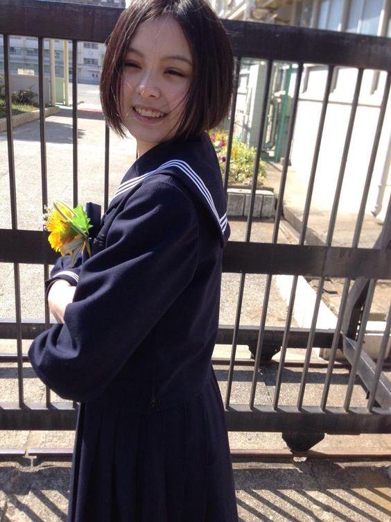 紺色のセーラー服を着て笑っている渡邊璃生の画像
