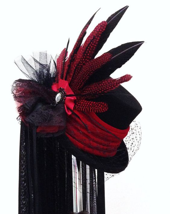 Black top hat with red velvet band, side attachment of raven and red speckled feathers with ribbon and lace and raven brooch, side ribbons and waist