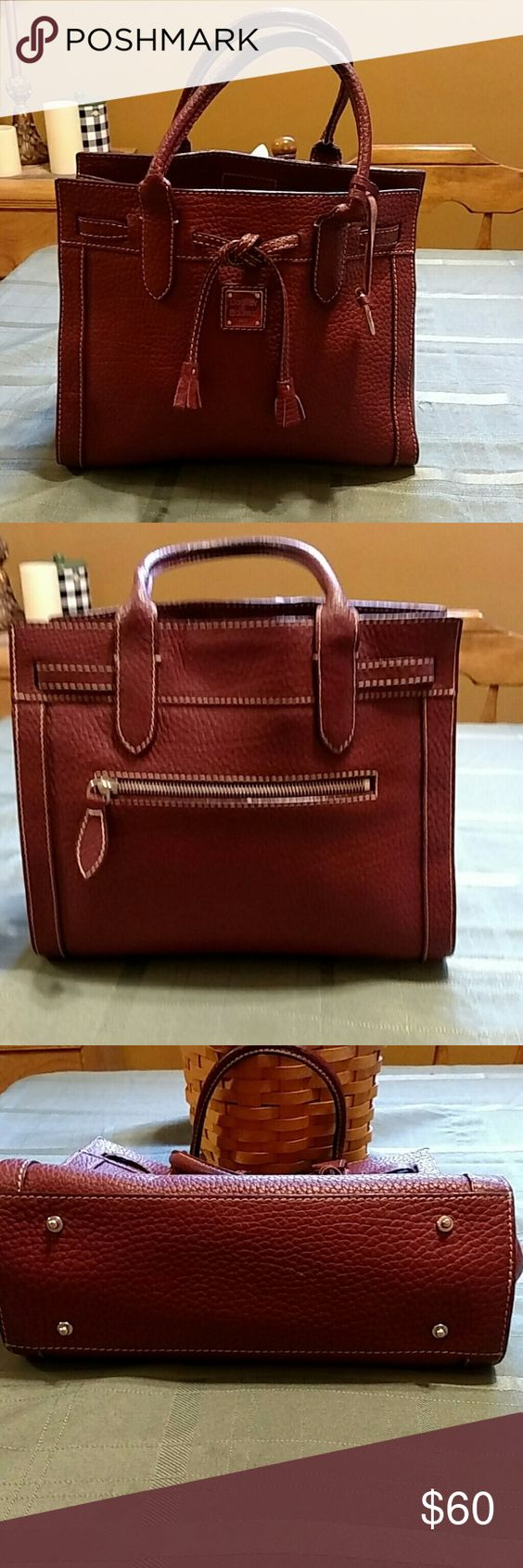 Authentic Dooney and Bourke tassel tote Gorgeous pebble grain leather in a rich wine color. Gold hardware and hanging DB emblem. Zippered compartment and slot inside. Mint condition. Dooney & Bourke Bags Satchels