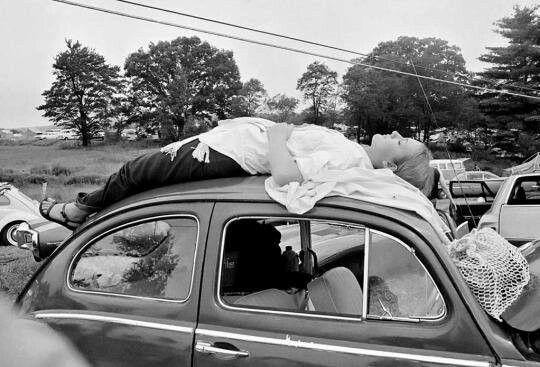 A girl naps on top of her car, while trying to reach the music festival at Woodstock, N.Y., Aug. 16, 1969.
