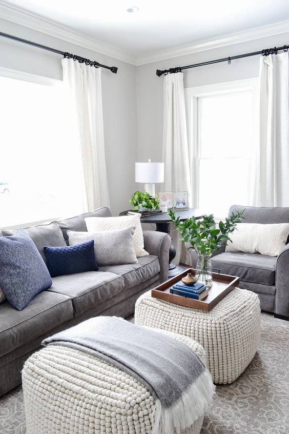 Gray Oak Studio - Hutchins Project Living Room - Modern Cozy - Gray Oak Studio - Hutchins Project Living Room - Modern Cozy - Neutral palette (gray, beige, ivory, cream), pops of blue and black. We updated hardware on media console, used lots of texture in 2 matching poufs in place of a traditional coffee table, brass and wood accents for interest and plants in every nook. Rejuvention light fixture. Nimbus by Benjamin Moore. Basket storage. Grid gallery wall.