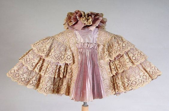 1897-1898, America  Cape by H&S Pogue Company  Lace, silk taffeta Kent State University Museum I really like the pink and the beige together, i think the pink really makes this cape stand out.