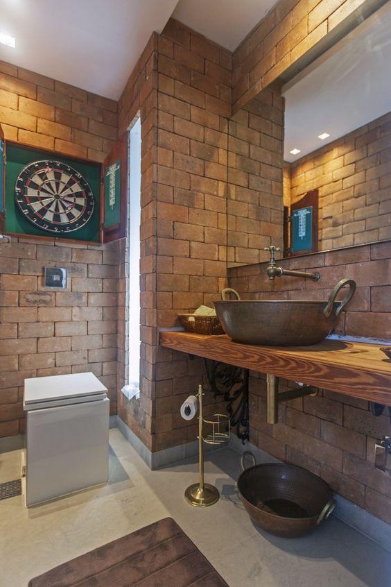 Lavabo rústico, com parede de tijolinho e bancada de madeira.: