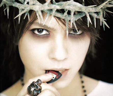 トゲのある蔦とピックを噛んでいるL'Arc〜en〜Ciel・hydeの画像