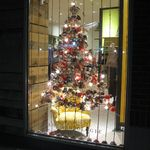 """For my first holiday windows, I created """"bauble trees"""" made completely from ornaments, pinecones, die cuts, cupcake wrappers, and other trinkets. To achieve the effect, I strung colorful ropes 5"""" apart and attached the baubles to them in the shape of trees."""