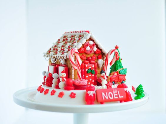 Bright red decorated gingerbread house with Noel sign