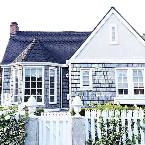 Darling shingled nantucket style home with a white picket for Nantucket shingles
