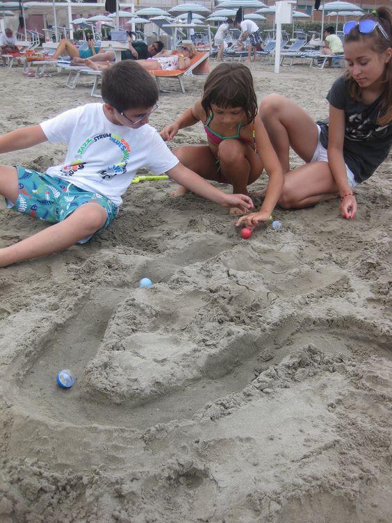 I suggerimenti dell'animazione sui giochi da provare in spiaggia sono sempre graditi dai bambini... guardate come si divertono con le biglie!