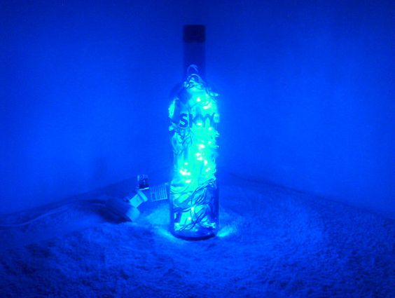 A blue glow comes from this LED bottle lamp, made from a Skyy Vodka bottle by RepurposedNV on Etsy.