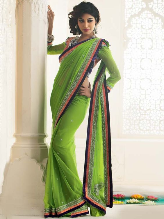 Get a royal look in this gorgeous green chiffon sari. The saree is enriched by the beautiful border and designer work with stone, embroidery and motis on it which differentiates it from other sarees. The saree has minute stones all over it. It is teamed with a matching blouse for making the saree a must buy. (Slight variation in color is possible)