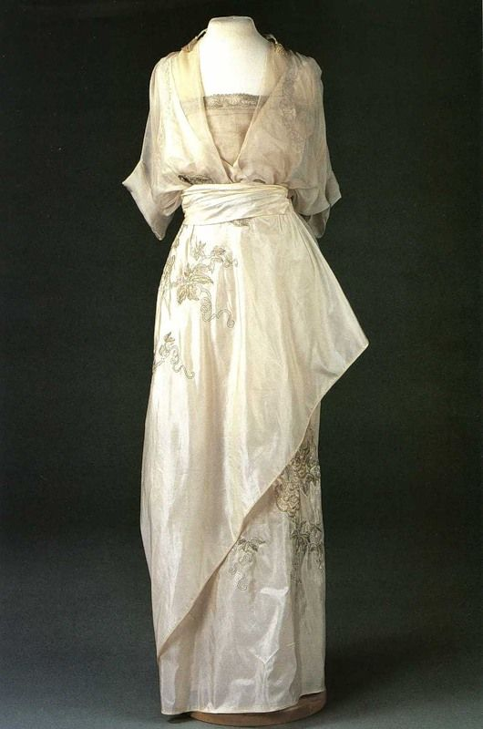"Embroidered white silk satin evening dress with chiffon overlay and silver braid trim, by Nadezhda ""Hope"" Lamanova, Russian, 1910."