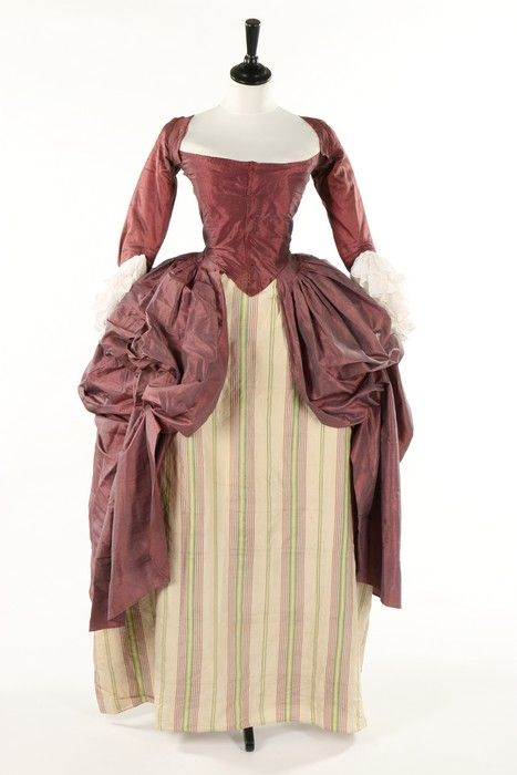 A shot mauve/grey silk robe a la polonaise, late 1770s, with boned, low pointed back panels, internal skirt loops, the sleeves applied with 1770s double tiered embroidered muslin engageants; together with a modern stomacher and a good panel of 1770s mauve and green striped silk, Provenance: the late Harry Matthews.