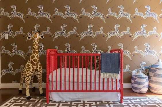 Amazing nursery with Scalamandre Zebra Print wallpapered accent wall features a red Jenny Lind Crib flanked by blue Senegalese hamper baskets and a Melissa & Doug Plush Giraffe atop a brown geometric rug.: