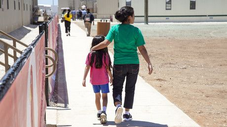 Residents walk through common campus area at the South Texas Family Residential…