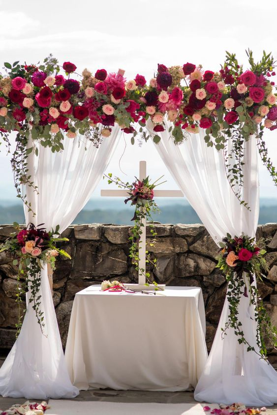 Stunning floral arbor for the ceremony | Mountain Wedding with Pops of Cranberry & Vibrant Florals + Local Beer & Homemade Apple Butter -- Bustld | NC wedding, mountain wedding, mountain bride, cranberry wedding inspiration | Photographer: @coreycagle, Venue: The Grove Park Inn Resort and Spa, Planner: Mary Bell Events, Florist: @ncflowergallery, Band: @eastcoastpins, Beauty: Bella Chic Salon & POP of Color, Rentals: Classic Event Rental, Lighting: LimeLig #weddingceremony