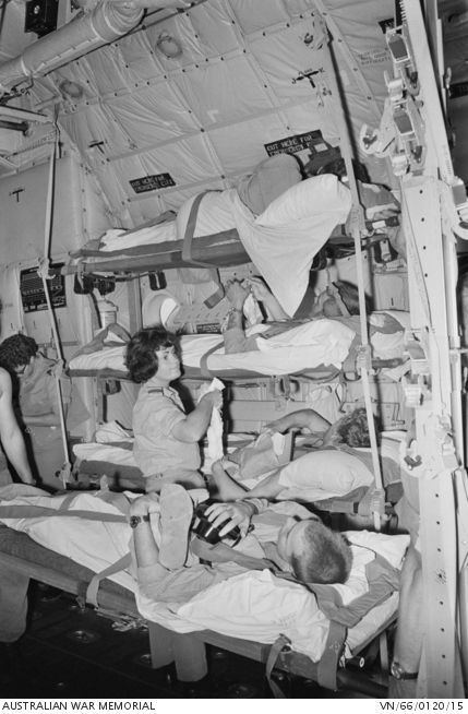 Several unidentified Australian soldiers lie strapped to their stretchers in a tiered formation inside a RAAF Hurcules aircraft, whilst two nurses check on them prior to their flight to either Saigon or Butterworth for recuperation. All personnel are unidentified. 1966