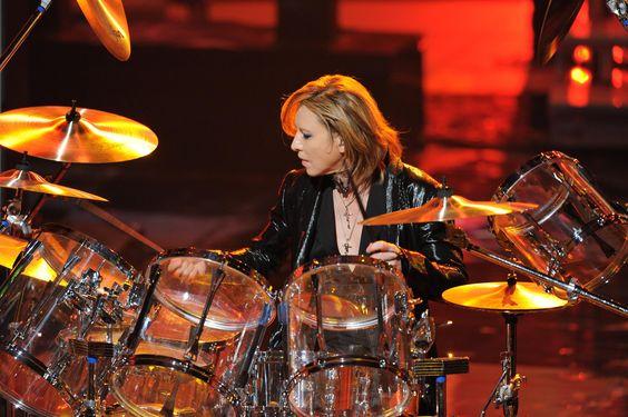 ステージで透明なドラムセットを叩いているXJAPAN・YOSHIKIの画像