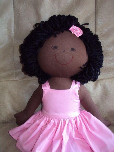 Boneca negra: corpo em tecido ou malha, com enchimento de fibra siliconizada e cabelos em lã.  Vestido em tricoline. R$ 60,00: