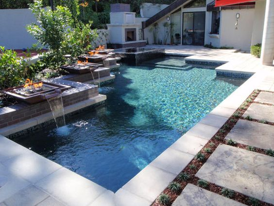The fire bowls next to the pool are filled with black glass and mirror pieces that reflect glow.