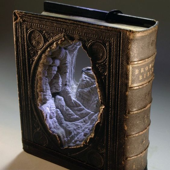 carved book sculpture by Guy Laramee. the white portion is ACTUALLY carved out from its pages.