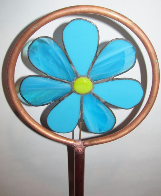 This garden stake stands roughly 3.5 feet tall and 7 inches wide. Made using copper plumbing pipes and stained glass. The flower is attached to it in a way that allows it to spin, adding a fun twist to beautiful garden decoration. Please keep in mind that due to color variations of the glass your product may not look exactly like the product pictured.    Can be made in the colors shown or you can choose your own custom colors for no extra cost. Just click on Request a custom order…