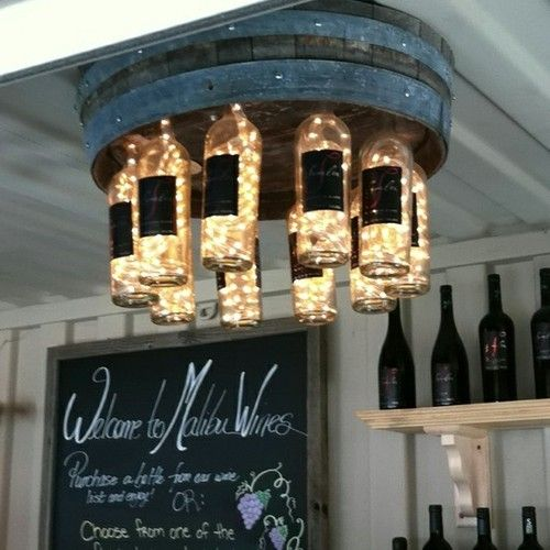 Chandelier made with a wine barrel, empty wine bottles and strands of Christmas lights...