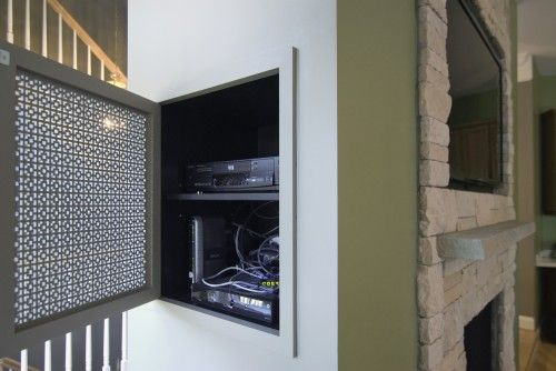 """The firm inserted a patterned panel into a cabinet door, and attached it to the allotted space. """"This niche not only hides all of the wires for a nice, clean look,"""" says Summit's design consultant Emily Miner, """"but it also allows for heat and air circulation for the electrical components."""""""