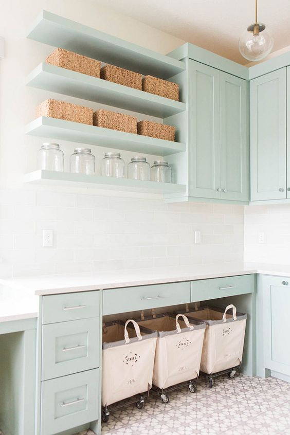 Laundry Room Design. Laundry room features gray green cabinets paired with white quartz countertops and a white glass subway tiled backsplash. Laundry room with three Steele Canvas laundry carts tucked below a countertop placed under stacked gray green floating shelves filled with woven baskets and vintage jars illuminated by a brass and glass globe pendant. #LaundryRoom Ashley Winn Design.