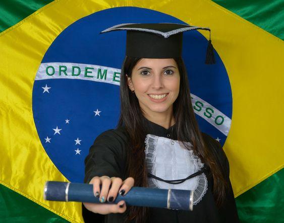 Foto com a Carol vestida com a beca de formatura, segurando o diploma e com a bandeira do Brasil de fundo.